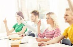 Grupp av studenter som lyfter händer Tonåringar i ett klassrum Arkivfoton