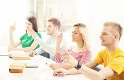 Grupp av studenter som lyfter händer Tonåringstudie i ett klassrum Arkivfoto