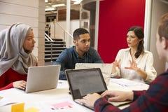 Grupp av studenter som möter för orubbligt med läraren arkivfoton