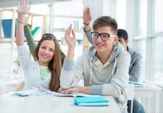 Grupp av studenter som tillsammans sitter i klassrum Royaltyfri Bild