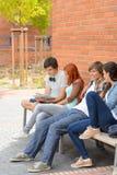 Grupp av studenter som ut hänger vid högskolan Royaltyfri Fotografi