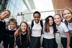 Grupp av studentvänner som ler tillsammans lycka royaltyfri foto