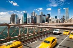 Grupp av suddiga typiska gula New York taxiar som korsar den Brooklyn bron med den Manhattan horisonten med blå himmel med få mol Arkivbilder
