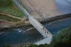 Grupp av surfare som korsar en near strand för bro royaltyfria bilder
