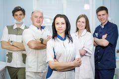 Grupp av tandläkare som står i deras kontor och ser kameran royaltyfria bilder