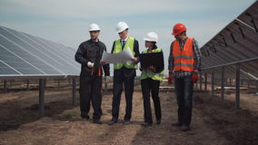 Grupp av teknikerer eller tekniker på en sol- lantgård lager videofilmer
