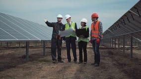 Grupp av teknikerer eller tekniker på en sol- lantgård Arkivfoto