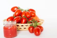 Grupp av tomater i en korg med tomatfruktsaft Royaltyfri Bild