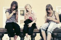 Grupp av tonåriga flickor som kallar på mobiltelefoner Arkivfoton