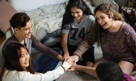 Grupp av tonåringar i ett sovrum som tillsammans sätter deras händer gemenskap- och teamworkbegrepp royaltyfri foto