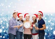 Grupp av tonåringar i santa hjälpredahattar med klockan Royaltyfri Foto
