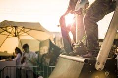 Grupp av tonåringar med deras skateboarder på rampdeltagandet i konkurrens under en solnedgång arkivfoto