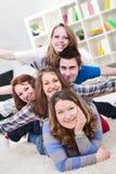 Grupp av tonåringar som har gyckel inomhus royaltyfri foto
