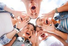 Grupp av tonåringar som ner ser och skriker Arkivfoto