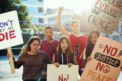 Grupp av tonåringar som protesterar begrepp för fred för rättvisa för hållande affischer för demonstration antiwar royaltyfria bilder