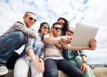 Grupp av tonåringar som ser minnestavlaPC Royaltyfri Fotografi