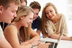 Grupp av tonåringar som tillsammans samlas runt om bärbara datorn Royaltyfria Foton