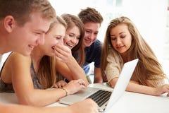 Grupp av tonåringar som tillsammans samlas runt om bärbara datorn Arkivfoton