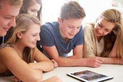 Grupp av tonåringar som tillsammans samlas runt om den Digital minnestavlan Royaltyfri Foto