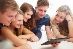 Grupp av tonåringar som tillsammans samlas runt om den Digital minnestavlan Fotografering för Bildbyråer