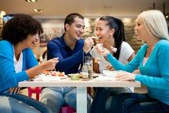 Grupp av tonåringar som tycker om i lunch arkivfoto
