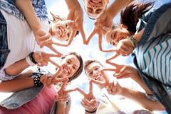 Grupp av tonåringar som visar finger fem Fotografering för Bildbyråer