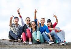 Grupp av tonåringar som visar finger fem Arkivbilder