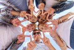 Grupp av tonåringar som visar finger fem Royaltyfria Bilder