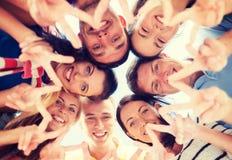 Grupp av tonåringar som visar gest för finger fem arkivbild
