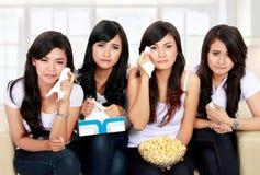 Grupp av tonåringen som håller ögonen på ledsen film Royaltyfri Fotografi