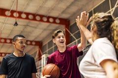Grupp av tonåringvänner på en basketdomstol som ger sig höga fem royaltyfria bilder