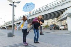 Grupp av tonåringvänner som har gyckel i staden som skrattar ungar med paraplyet Stads- tonårig livsstil royaltyfria foton