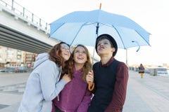 Grupp av tonåringvänner som har gyckel i staden som skrattar ungar med paraplyet Stads- tonårig livsstil fotografering för bildbyråer
