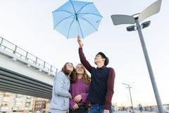 Grupp av tonåringvänner som har gyckel i staden som skrattar ungar med paraplyet Stads- tonårig livsstil royaltyfria bilder