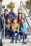 Grupp av tonårs- elever utanför klassrum Arkivfoto