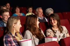 Grupp av tonårs- flickor som håller ögonen på filmen i bio Arkivbilder