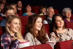 Grupp av tonårs- flickor som håller ögonen på filmen i bio Royaltyfria Bilder