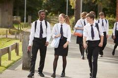 Grupp av tonårs- studenter i enhetliga utvändiga skolabyggnader royaltyfri foto