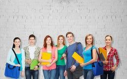 Grupp av tonårs- studenter med mappar och påsar Arkivbilder