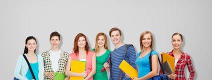 Grupp av tonårs- studenter med mappar och påsar royaltyfria foton