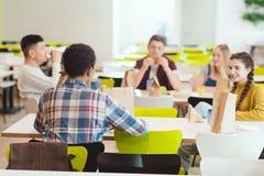 grupp av tonårs- studenter som pratar, medan ta lunch royaltyfria bilder