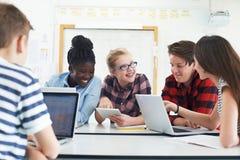 Grupp av tonårs- studenter som samarbetar på projekt i IT-grupp royaltyfri fotografi