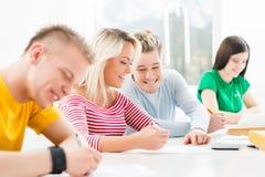 Grupp av tonårs- studenter som studerar på kursen i klassrumet Arkivbild
