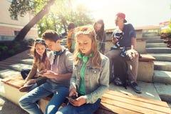 Grupp av tonårs- vänner med smartphones utomhus royaltyfri fotografi