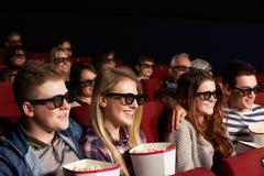 Grupp av tonårs- vänner som håller ögonen på filmen 3D Royaltyfri Bild