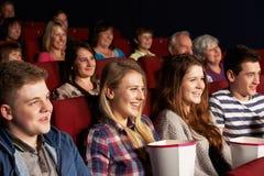 Grupp av tonårs- vänner som håller ögonen på filmen i bio Fotografering för Bildbyråer