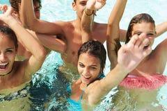 Grupp av tonårs- vänner som har gyckel i simbassäng Arkivbilder