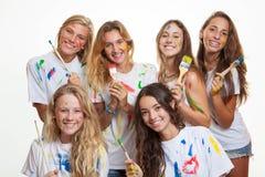Grupp av tonåringar som har gyckel med målarfärg Arkivfoto