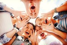 Grupp av tonåringar som ner ser och skriker Arkivfoton