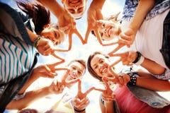 Grupp av tonåringar som visar finger fem Arkivfoto